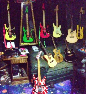 LEFT TO RIGHT: Ibanez 777DY, 777LNG, 777SK, YJM Strat (custom made), 12 string acoustic, original 1989 RG 570. Sofa: Carvin thinline acoustic, Epiphone Joe Perry Les Paul, Ibanez Acoustic, and finally the EVH 5150.