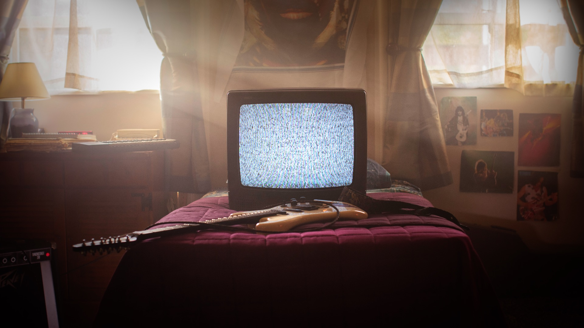 Analog television on a bed with a guitar